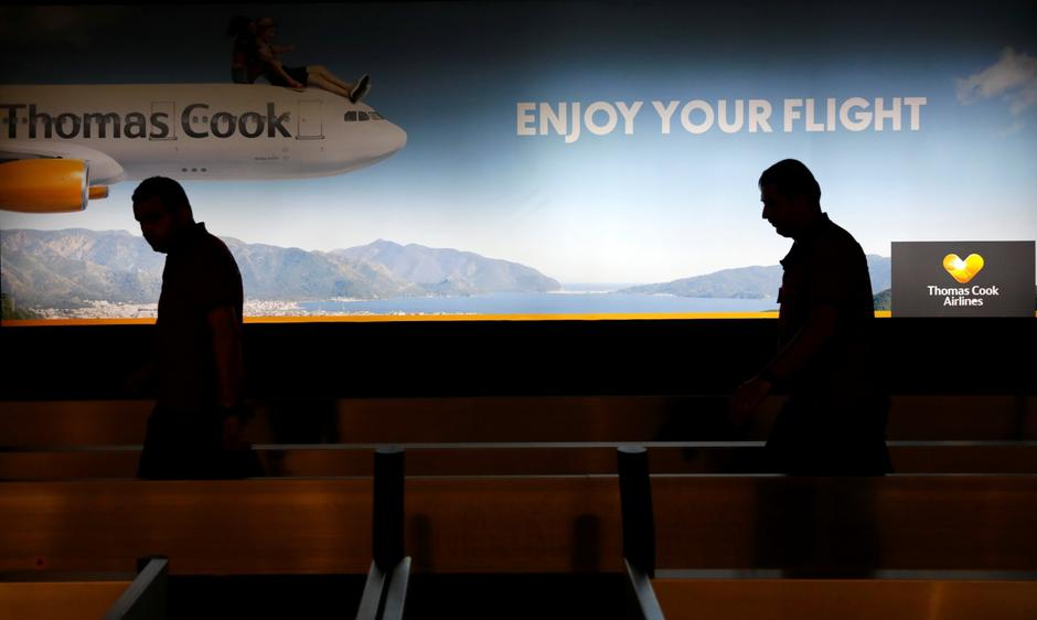 Men walk past a Thomas Cook banner at Dalaman Airport | Autor: UMIT BEKTAS/REUTERS/PIXSELL/REUTERS/PIXSELL