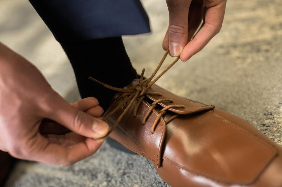 Tying strings of formal brown shoes | Autor: NEXT LEVEL PHOTOGRAPHY, LLC