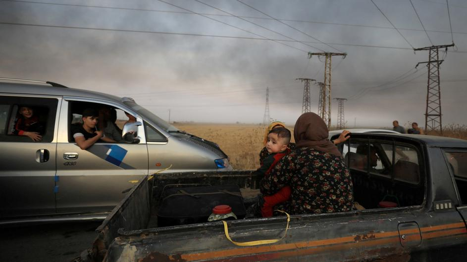A woman with a baby sits at a back of a truck as they flee Ras al Ain town