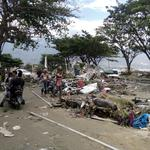 Resident checks dead bodies to find their family at a street after tsunami hit in Palu