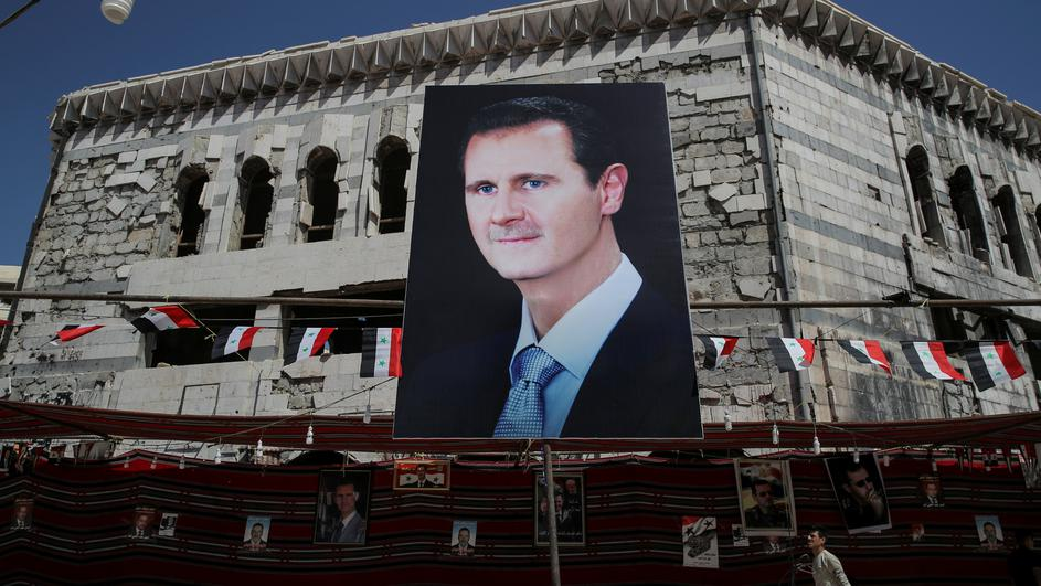FILE PHOTO: A banner depicting Syrian President Bashar al-Assad in Douma, outside Damascus, Syria