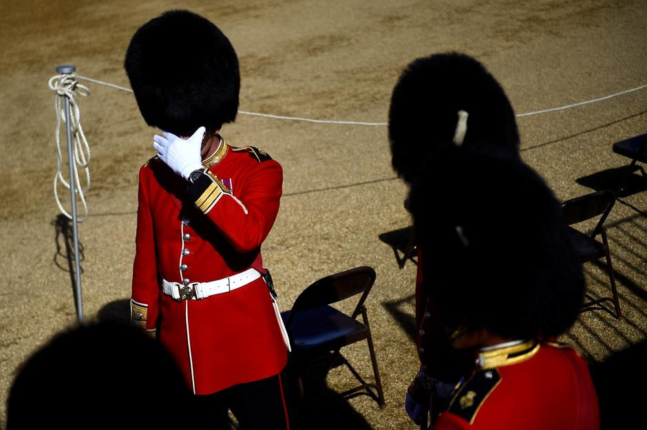 A guard member shields his eyes from the sun before the Household Division rehearse Trooping the Colour for the Colonel's Review ahead of the Queen's birthday parade next week, on Horseguards Parade in London | Autor: Clodagh Kilcoyne/REUTERS/PIXSELL/REUTERS/PIXSELL