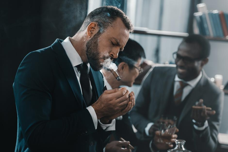businessman smoking cigar with multicultural business team | Autor: Dreamstime