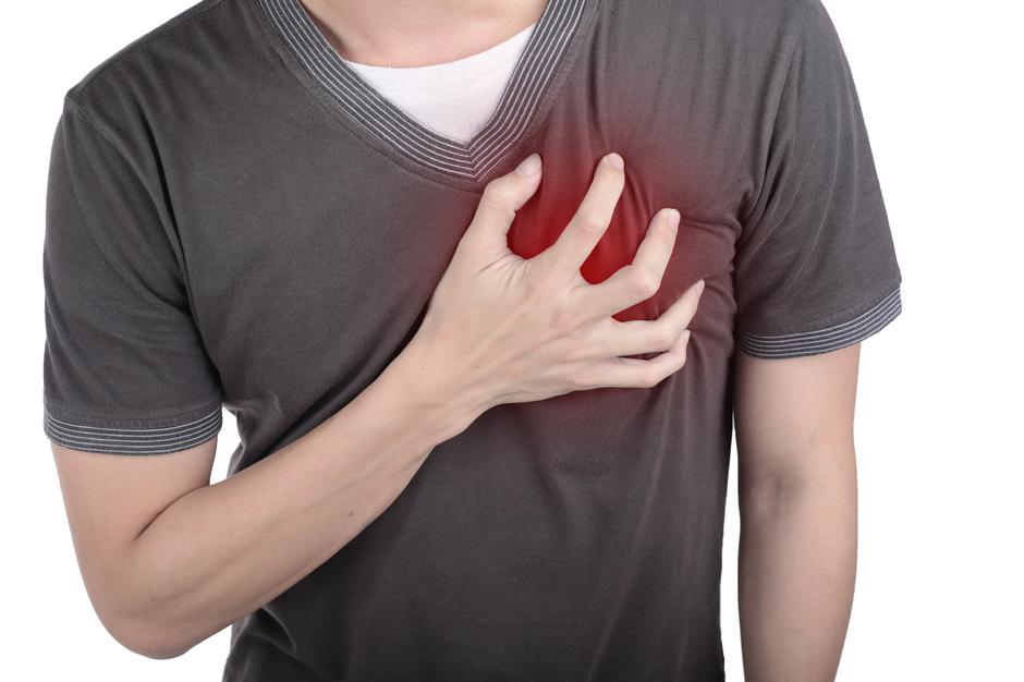 Young man holding his heart to this pain.  | Autor: dreamstime