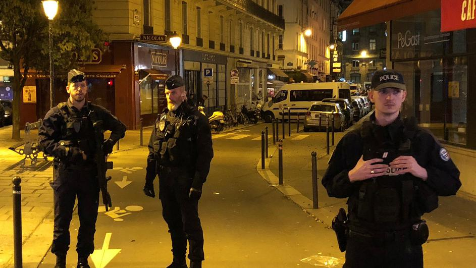 French police secure a street after a man killed a passer-by in a knife attack in the heart of Paris and injured four others before being shot dead by police