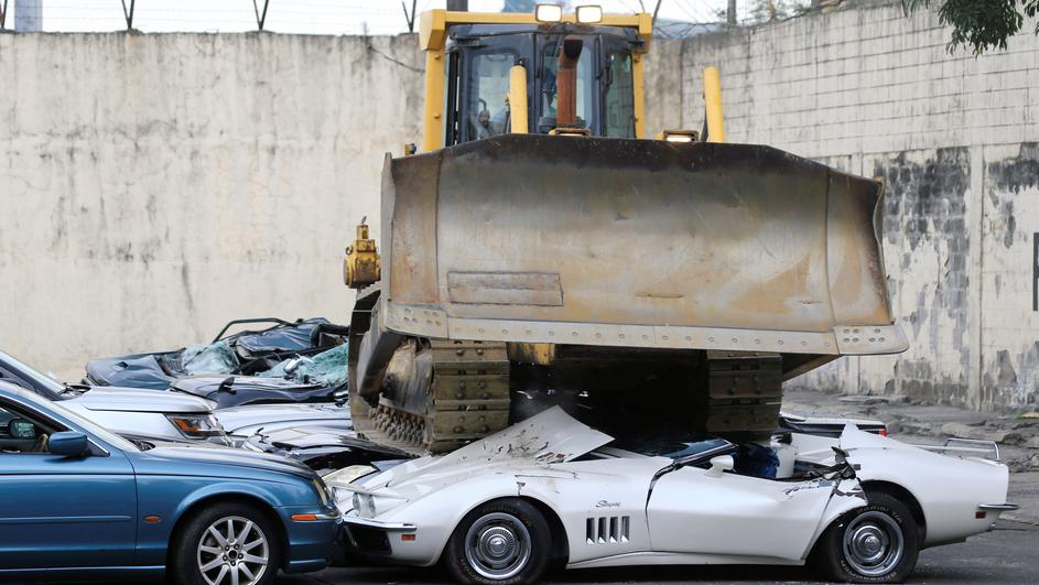 A bulldozer destroys condemned smuggled luxury cars worth 61,626,000.00 pesos during the 116th Bureau of Customs founding anniversary in Manila