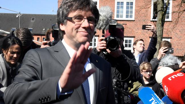 Catalonia's former leader Carles Puigdemont waves to the media as he leaves the prison in Neumuenster