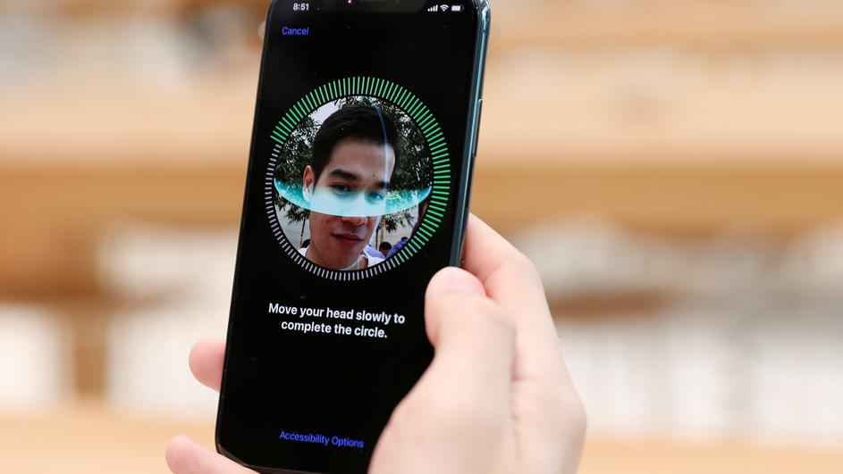 A customer sets up his iPhone X Face ID during its launch at the Apple store in Singapore