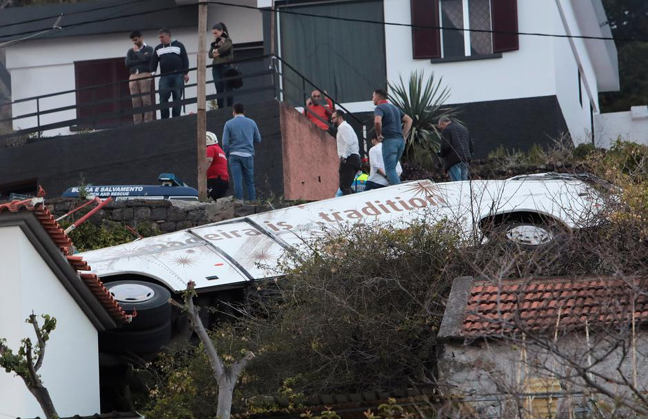 People stand next to the wreckage of a bus after an accident in Canico | Autor: DUARTE SA
