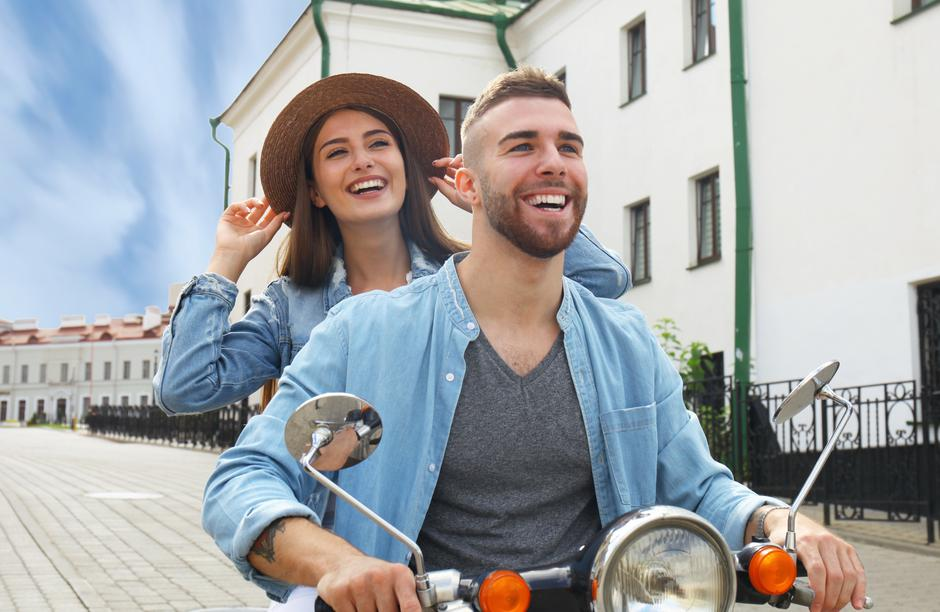 happy young couple riding scooter in town. Handsome guy and young woman travel. Adventure and vacations concept. | Autor: Dreamstime