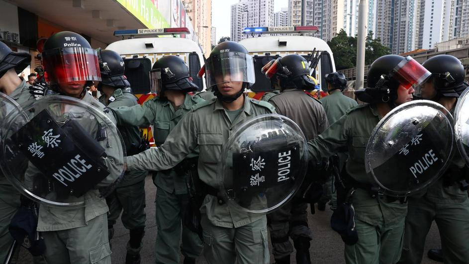 Riot police stand guard near Amoy Plaza shopping mall in Kowloon Bay, Hong Kong