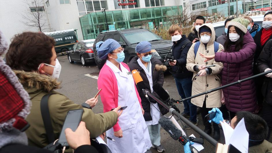 Medical workers wearing face masks speak to journalists outside a hospital where three patients cured of the novel coronavirus were discharged, in Beijing