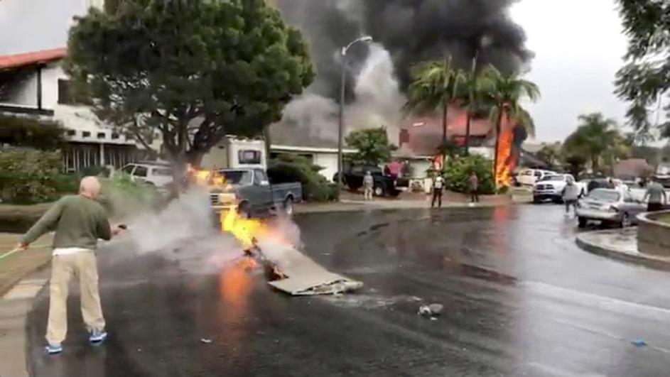 A man puts out fire on a piece of debris from a plane that crashed into a house in a residential neighborhood in Yorba Linda, California