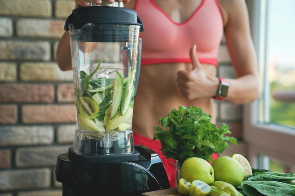 close up of young woman with blender and green vegetables making detox shake or smoothie at home | Autor: Nataliya Petrovich