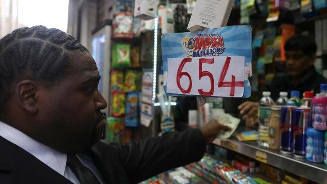A man buys Mega Millions lottery tickets for Tuesday's drawing after jackpot rose over $650 million in New York