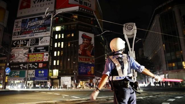 A police officer is seen during blackout after a powerful earthquake hit the area at a cross-point in Sapporo