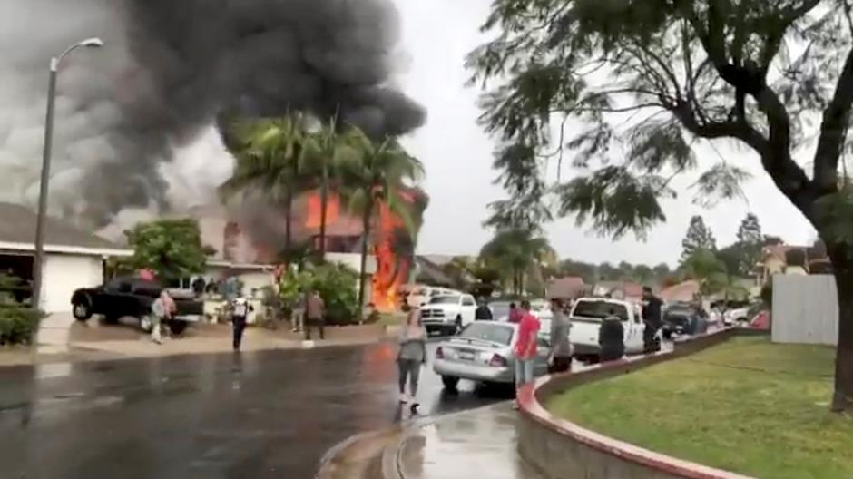 People look as smoke billows after a plane crashed into a house in a residential neighborhood in Yorba Linda, California | Autor: SOCIAL MEDIA