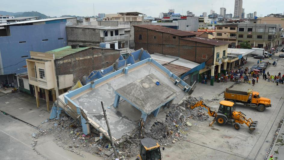 The debris of a collapsed house is cleared after an earthquake struck off the Pacific coast, in Guayaquil