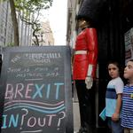 "Children pose next to a chalkboard advertising a Brexit viewing event at ""The Churchill Tavern"", a British theme bar, on the day where Britain votes whether or not to remain in the European Union in the Manhattan borough of New York"