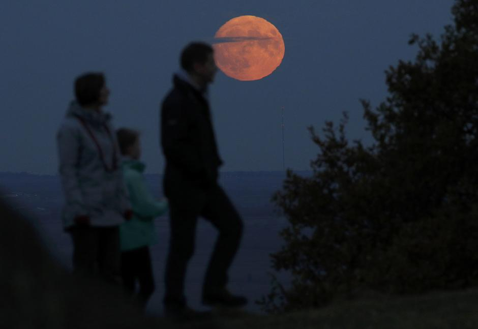 "A family watch the moon rise a day before the ""supermoon"" spectacle on Beacon Hill near Loughborough 
