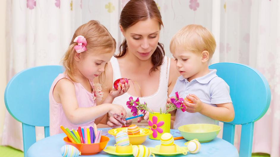 Mother with kids paint Easter eggs