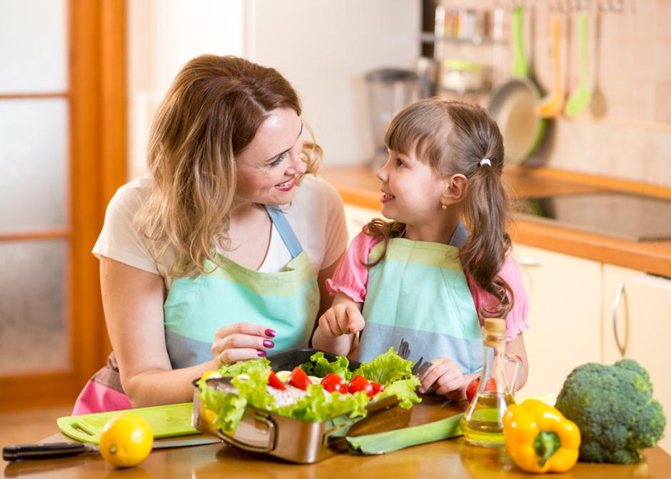 mother and kid cooking and having fun in kitchen | Autor: Dreamstime