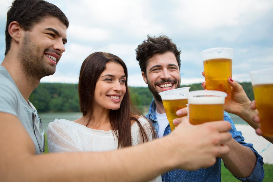 Group of friends holding beers and making a toast | Autor: Tuned_In