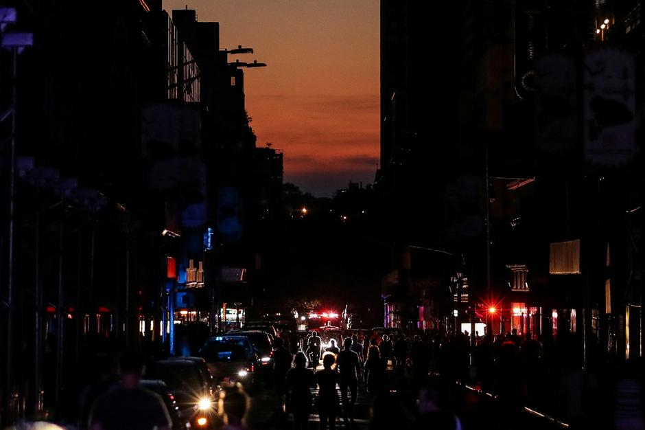 People walk along a dark street near Times Square area, as a blackout affects buildings and traffic during widespread power outages in the Manhattan borough of New York | Autor: JEENAH MOON/REUTERS/PIXSELL/REUTERS/PIXSELL
