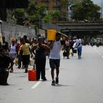 People walk on a highway, carrying containers with water collected from a sewage drain in Caracas