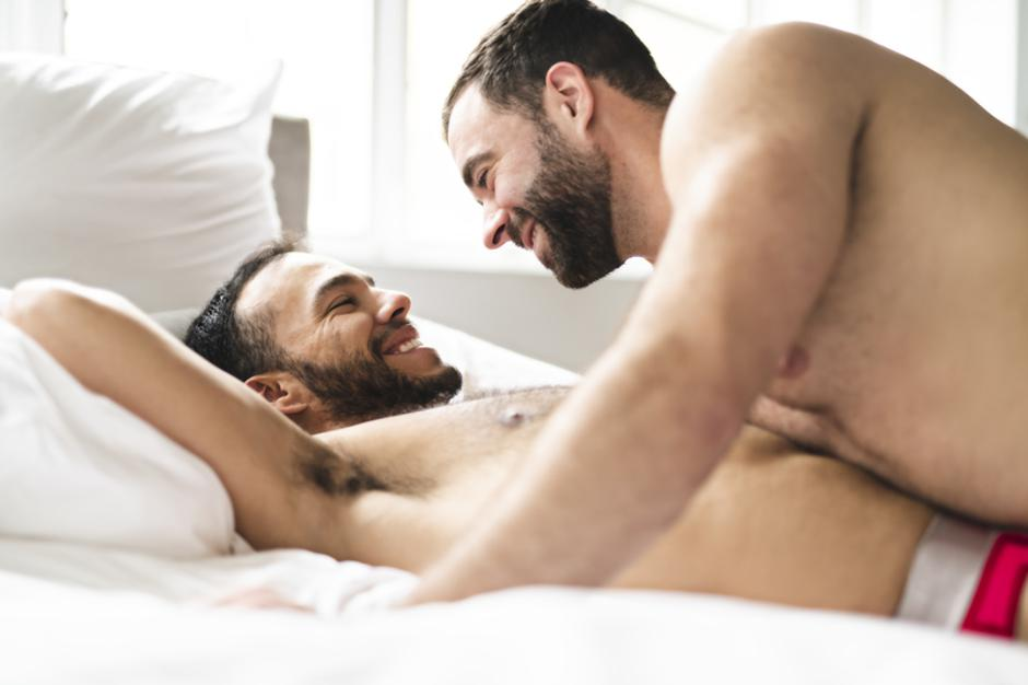 A Handsome gay men couple on bed together | Autor: Dreamstime