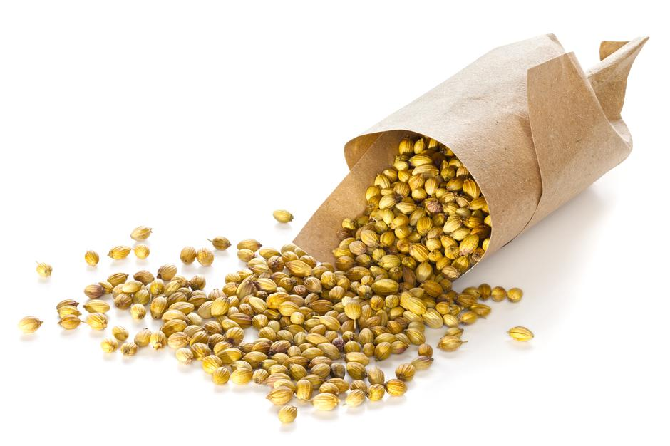 Coriander Seeds Spilling from Brown Paper Cone | Autor: Dreamstime
