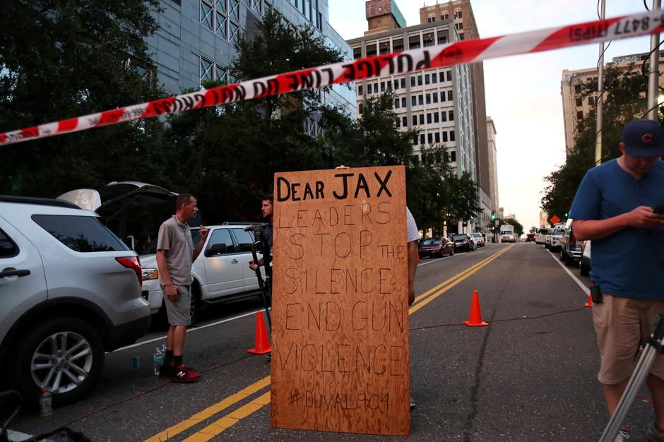 A man holds a sign in support of gun control outside of The Jacksonville Landing after a shooting in Jacksonville | Autor: JOEY ROULETTE