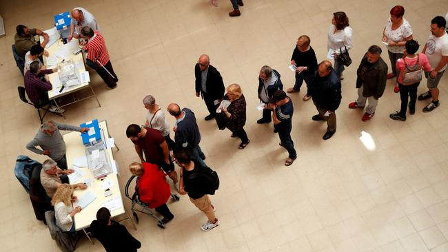 People queue to cast their votes for the European Parliament and local elections at a polling station in Barcelona