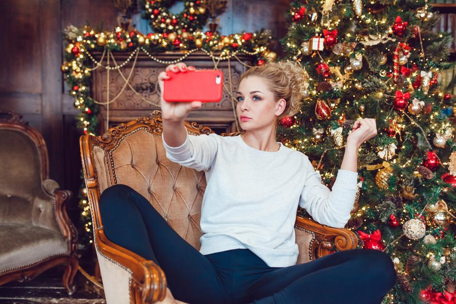 Young pretty blonde woman sitting on a chair near Christmas | Autor: Kanashkin