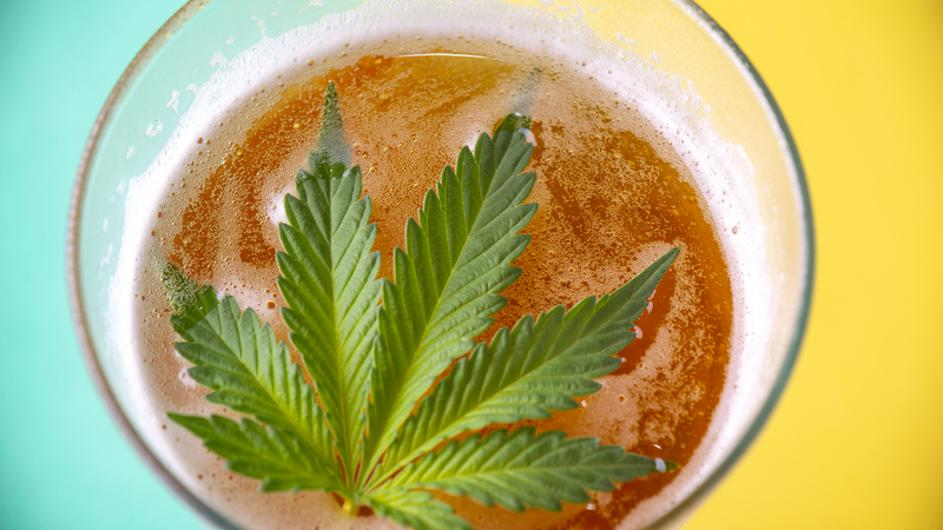 Detail of cold glass of beer with cannabis leaf