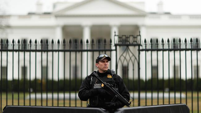A uniformed Secret Service officer is pictured on scene after a passenger vehicle struck a security barrier near the White House in Washington