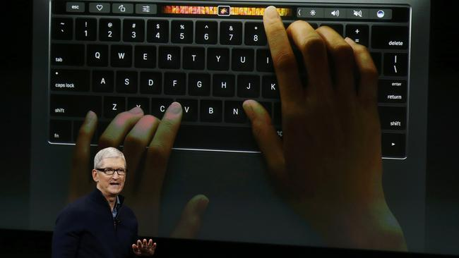 Apple CEO Tim Cook speaks under a graphic of the new MacBook Pro during an Apple media event in Cupertino