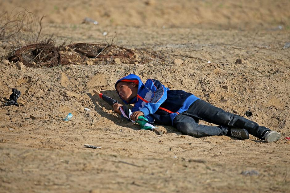 Palestinian boy takes cover from Israeli fire during an anti-Israel protest in the southern Gaza Strip | Autor: IBRAHEEM ABU MUSTAFA/REUTERS/PIXSELL/REUTERS/PIXSELL