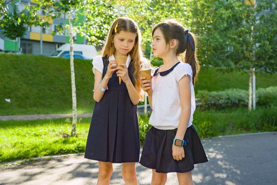 Portrait of two girlfriends schoolgirls 7 years old in school uniform eating ice cream. | Autor: Valerii Honcharuk