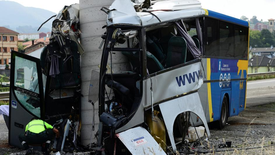 A civil guard surveys the wreckage of a bus crash which left at least four people dead in Aviles