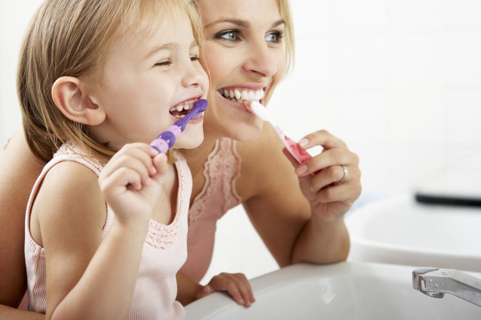 Mother And Daughter Brushing Teeth Together | Autor: bowdenimages