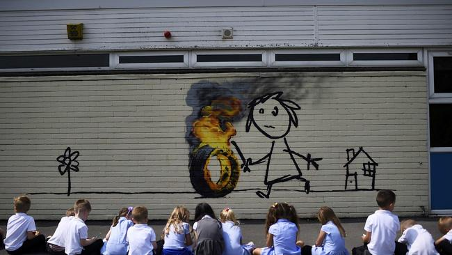Reception class school children sit in a row as they draw a mural attributed to Banksy in Bristol