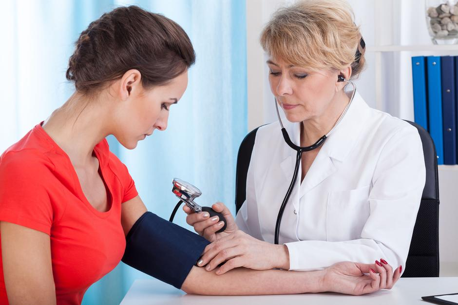 Taking blood pressure of female patient  | Autor: