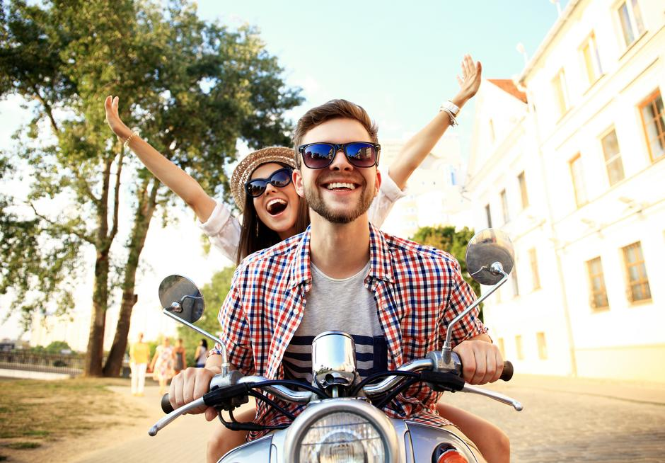 Portrait of happy young couple on scooter enjoying road trip | Autor: opolja