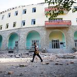 A police officer walks past a damaged building after an earthquake in Tirana