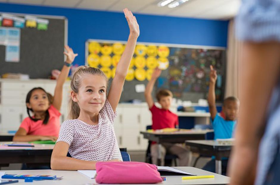 Children raising hands in classroom | Autor: Dreamstime