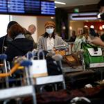 Travellers wearing masks arrive on a direct flight from China, in Paris