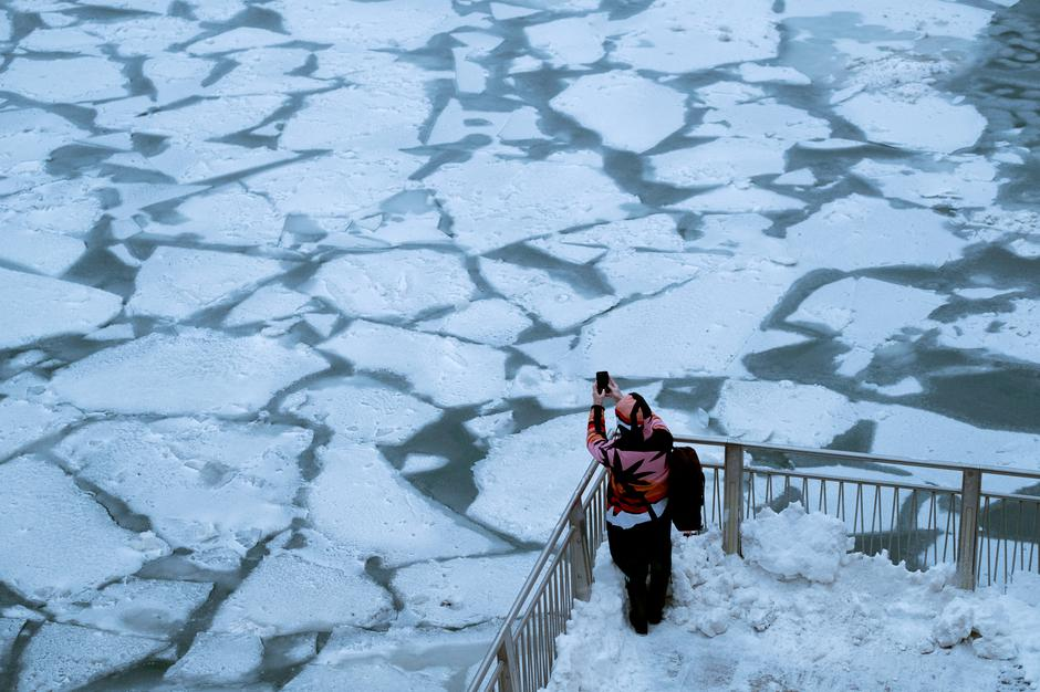 A pedestrian stops to take a photo by Chicago River as bitter cold phenomenon called the polar vortex has descended on much of the central and eastern United States | Autor: STRINGER