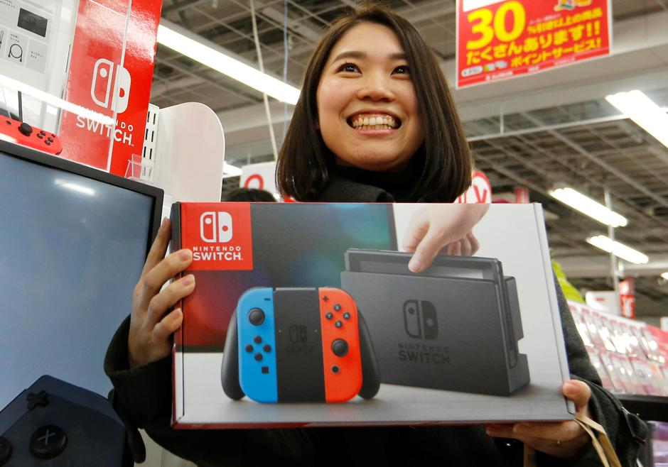 Nao Imoto smiles as she poses with her Nintendo Switch game console after buying it at an electronics store in Tokyo | Autor: TORU HANAI