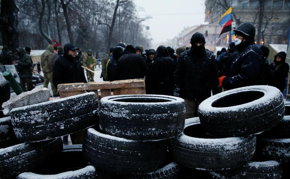 Anti-government protesters stand behind a barricade next to the Parliament building in Kiev | Autor: GLEB GARANICH